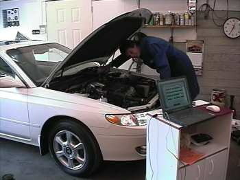 Henry inspects fuel injection system, with laptop connected to OBD system